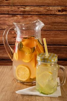 Grande brocca in vetro con acqua aromatizzata agli agrumi e limonata fatta in casa.