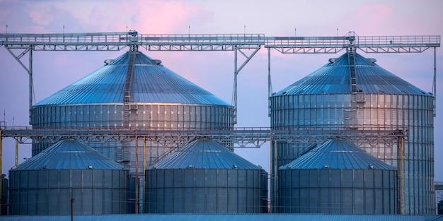 Grande complesso di stoccaggio e essiccazione del grano sullo sfondo del cielo serale