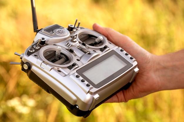Grande telecomando grigio con molte leve e pulsanti per controllare il drone. nella mano di un uomo. messa a fuoco selettiva, primo piano.