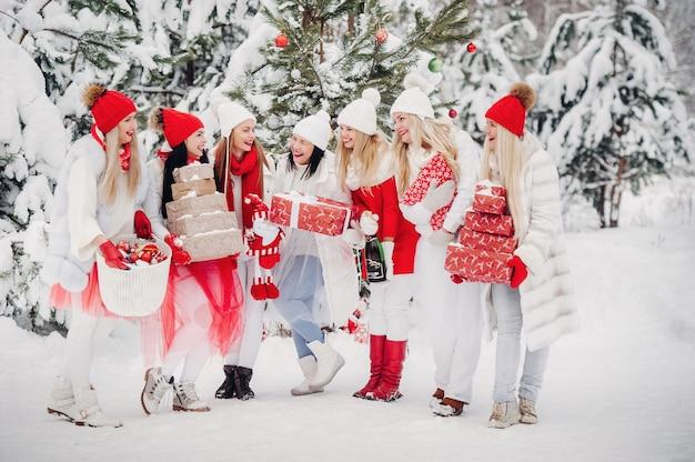 Un folto gruppo di ragazze con regali di natale nelle loro mani in piedi nella foresta invernale. ragazze in abiti rossi e bianchi con regali di natale nella foresta innevata.