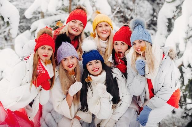 Un folto gruppo di ragazze con lecca-lecca in mano si trova nella foresta invernale. ragazze in abiti rossi e bianchi con caramelle in una foresta innevata.