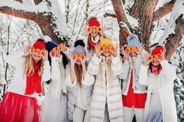 Un folto gruppo di ragazze con i mandarini sono in piedi nella foresta invernale. ragazze in abiti rossi e bianchi con frutta in una foresta innevata.