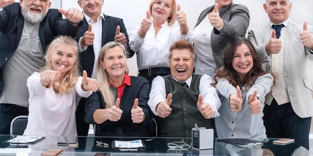 Un folto gruppo di dipendenti felici che mostrano il loro successo. il concetto di professionalità