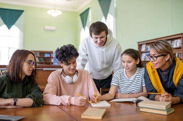 Folto gruppo di studenti adolescenti seduti alla scrivania nella biblioteca del college mentre discutono i punti del prossimo seminario