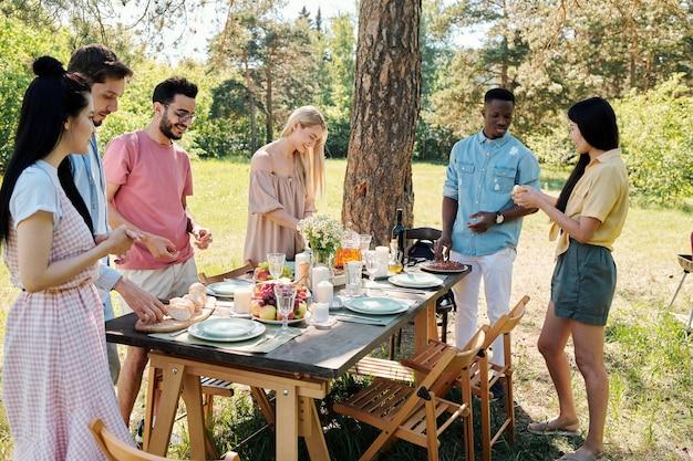 Un folto gruppo di giovani amichevoli interculturali in piedi sotto un pino mentre alcuni di loro parlano e gli altri servono la tavola festiva