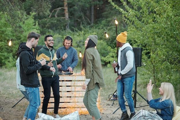 Grande gruppo di giovani amici allegri che ballano e si divertono nel fine settimana in un ambiente naturale bevendo birra e interagendo