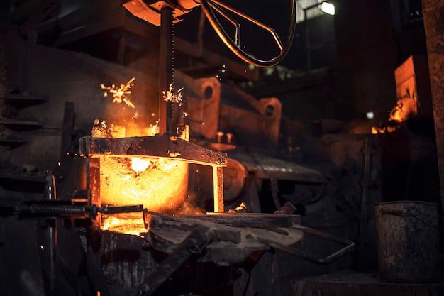 Grande forno industriale per fonderia con ferro caldo all'interno, attrezzature per metallurgia e industria pesante.
