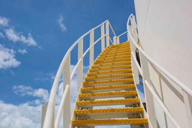 Grandi serbatoi industriali per olio con una passerella su e giù per le scale metalliche del serbatoio di stoccaggio dell'olio sul lato blu del cielo.