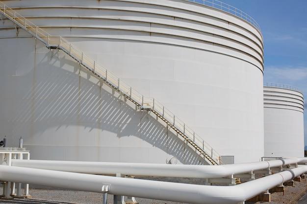 Grandi serbatoi industriali per olio con una passerella su e giù per le scale metalliche del serbatoio di stoccaggio dell'olio sul lato di un contenitore per olio industriale.