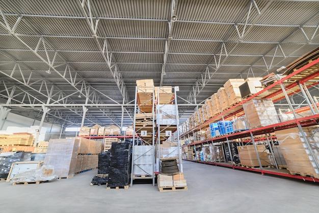 Ampio capannone industriale. scaffali lunghi con una varietà di scatole e contenitori.