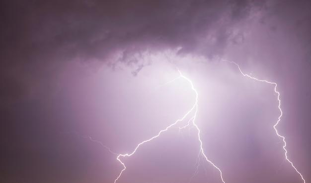 Grande scarica di fulmini nel cielo notturno durante un temporale, paesaggio con cielo illuminato dalla scarica di fulmini