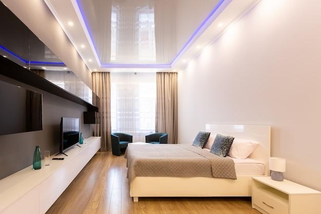 Ampio soggiorno con letto, mobili e tv in stile moderno