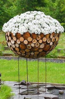 Grande lussureggiante bouquet di camomille bianche in una grande ciotola di legno sulla strada