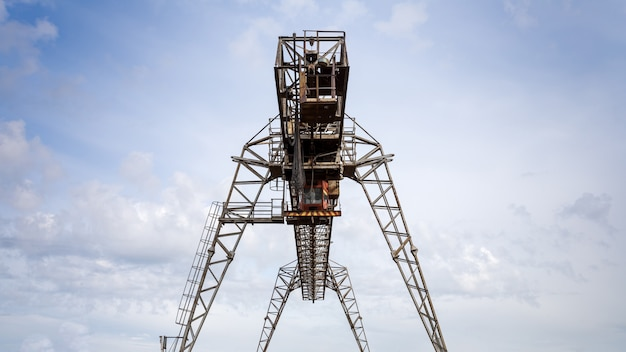 Grandi gru a cavalletto in metallo in un cantiere contro il cielo blu.