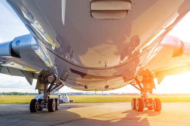 Grande aeroplano moderno vista dal basso verso il basso e carrello di atterraggio, luce del sole.