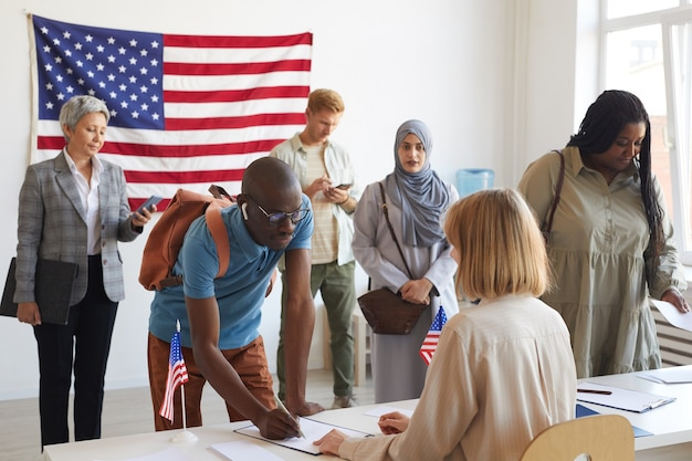 Grande gruppo multietnico di persone che si registrano al seggio elettorale decorato con bandiere americane il giorno delle elezioni, copia dello spazio