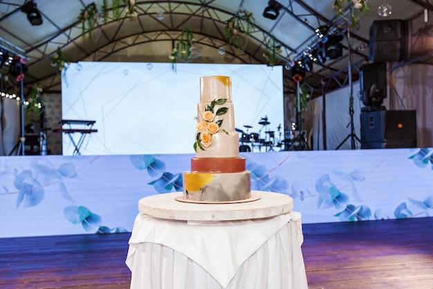 Grande torta nuziale multicolore multicolore con rose su un supporto di legno rotondo