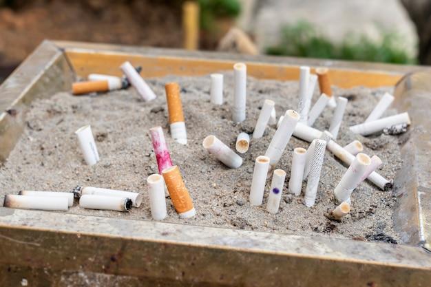 Un gran numero di mozziconi di sigaretta con filtro, spento in un'urna per strada nella sabbia. vre fumo, kkantsergens e cancro