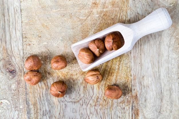 Un gran numero di nocciole sbucciate durante la cottura del primo piano della pianta viene utilizzato nelle nocciole alimentari delle persone in un cucchiaio di legno