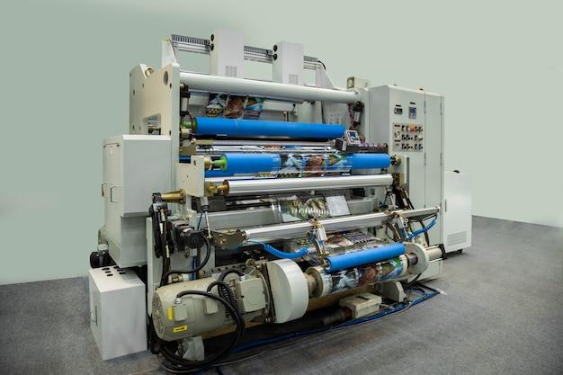 Grande macchina da stampa offset o rivista che esegue un lungo rotolo di carta nella linea di produzione della stampante industriale.