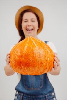 Grande zucca arancione matura nelle mani di una donna contadina sfocata concetto di agricoltura e halloween