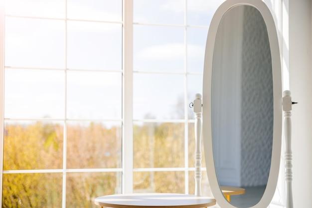 Un grande specchio ovale a figura intera si trova di fronte a una grande finestra. copia spazio
