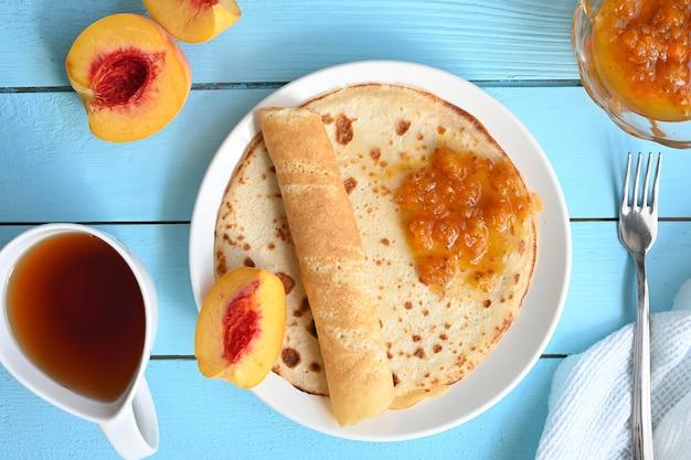 Grandi frittelle con marmellata, tè e pesche su sfondo blu. Foto Premium
