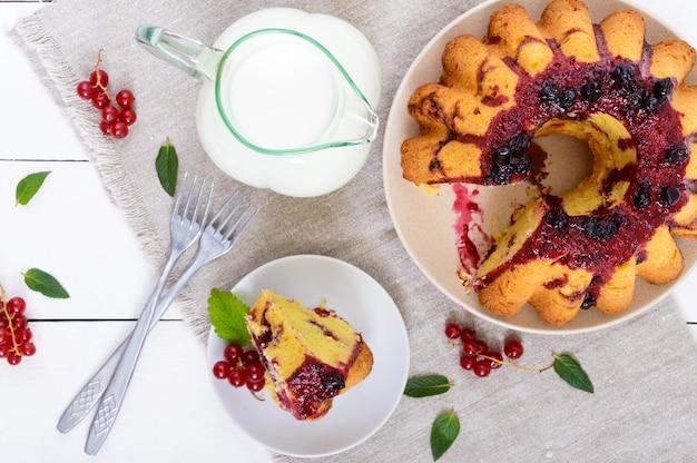 Un grande pezzo di torta di ricotta con frutti di bosco estivi, marmellata e una brocca di latte su bianco