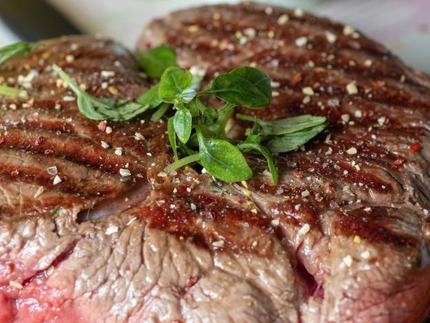 Un grosso pezzo di carne fresca e succosa cosparsa di spezie ed erbe aromatiche. strisce rare, il succo della carne. primo piano, vista frontale