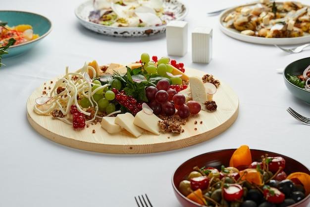 Grande piatto di formaggi assortiti al centro del tavolo con vari antipasti, mix di formaggi su un piatto di legno come antipasto principale in tavola.