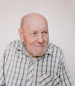 Un grande ritratto di un uomo anziano su uno sfondo chiaro con rughe profonde, macchie dell'età. vecchio nonno.