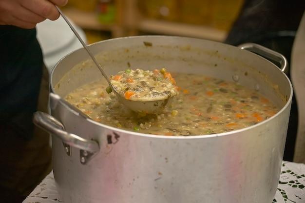 Grande pentola piena di zuppa di verdure e cereali pronta per essere servita ai commensali.