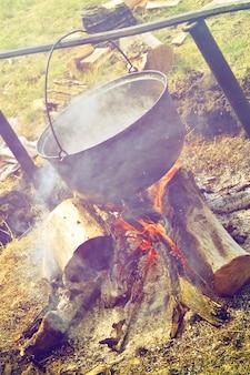 Pentola grande appesa sopra il fuoco da campo con fumo e legna da ardere, filtro fotografico