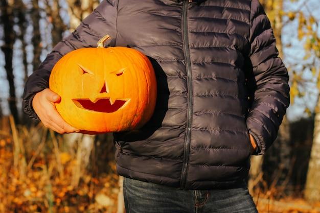 Una grande zucca nelle mani di un uomo, primo piano. concetto festa di halloween. mr jack o lantern