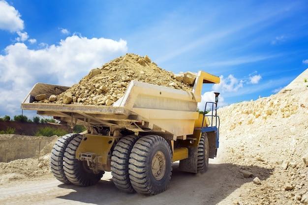 Un grande autocarro con cassone ribaltabile della cava caricato con la roccia