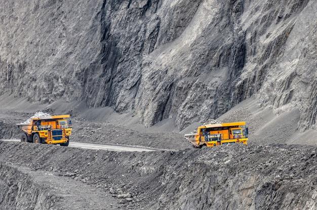 Autocarro con cassone ribaltabile di cava di grandi dimensioni. industria dei trasporti. un camion minerario sta guidando lungo una strada di montagna.
