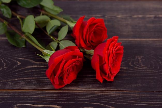 Grandi rose rosse su fondo in legno scuro.