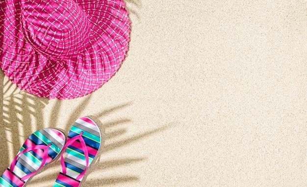 Grande cappello estivo rosa rotondo e sandali colorati a righe sulla sabbia con ombra di palma