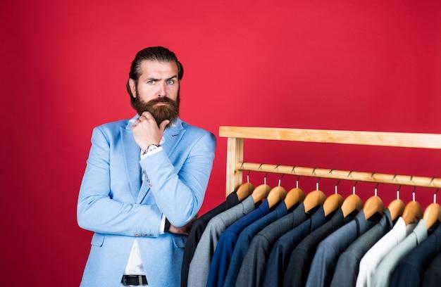 Ampia selezione di abiti da uomo. l'uomo barbuto sceglie la giacca sul gancio. concetto di guardaroba maschile. l'uomo va a fare shopping nel negozio di abbigliamento. il nostro studio atelier presenta qualsiasi stile di moda.