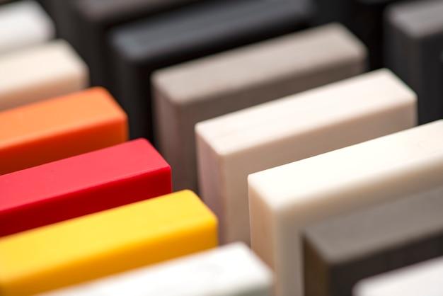 Ampia selezione di campioni di pietra per piani di lavoro e pavimenti. pezzi di pietra acrilica artificiale in una scatola di campioni. una serie di sfumature di controsoffitti di diverse trame