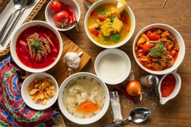 Un ampio set di diverse zuppe orientali. borscht con manzo e panna acida, lagman con agnello e adzhika, brodo di pollo shurpa e zuppa di pesce con verdure.