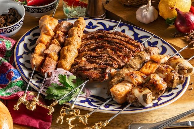 Un ampio set di diversi tipi di shish kebab su un piatto tradizionale uzbeko. shish kebab di agnello, pollo, salsicce fatte in casa, fegato e salmone.