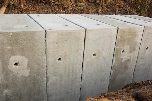Pozzetti quadrati in calcestruzzo di grandi dimensioni sono installati in cantiere; per il drenaggio dell'acqua piovana della strada principale; sfondo della costruzione civile