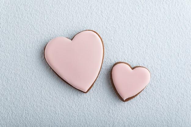 Biscotti grandi e piccoli a forma di cuore con zucchero a velo su sfondo bianco. festa della mamma. giornata della donna. san valentino.