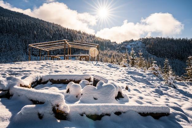Un grande falò coperto di neve per le escursioni nelle montagne dei carpazi i luminoso sole freddo