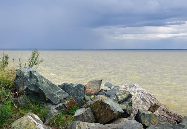 Grandi pietre sulla riva delle onde del mare ob sull'acqua sotto un cielo blu con nuvole drammatiche
