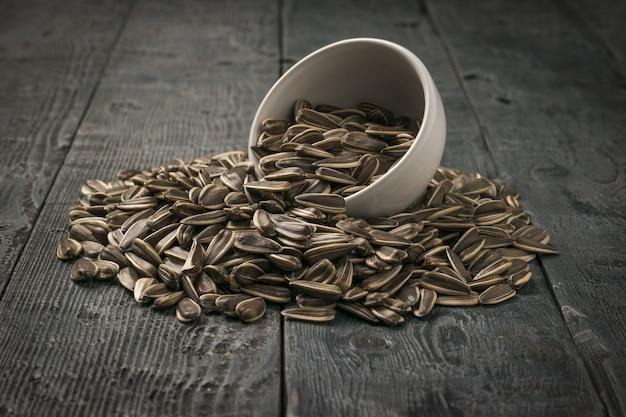 Grandi semi di girasole vengono versati da una ciotola di ceramica su un tavolo di legno. la fresca resa del girasole.