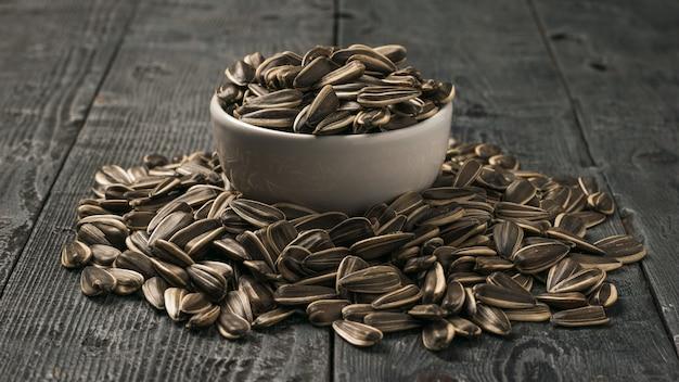 Grandi semi di girasole in una ciotola bianca e su un tavolo di legno. la fresca resa del girasole.