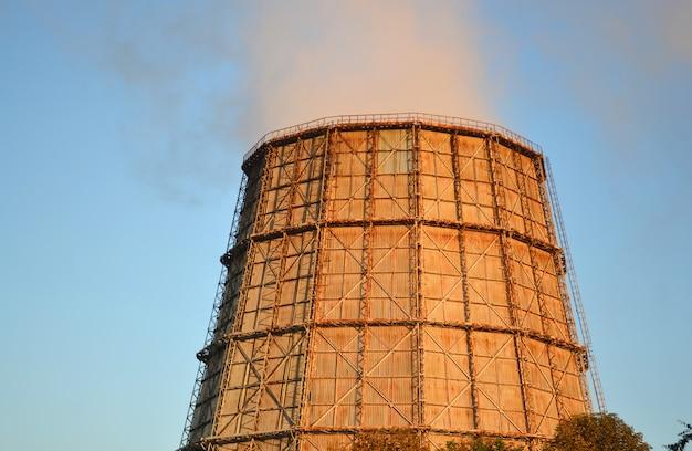 Grande centrale termica camino al tramonto dell'alba con cielo azzurro con il fumo dal camino