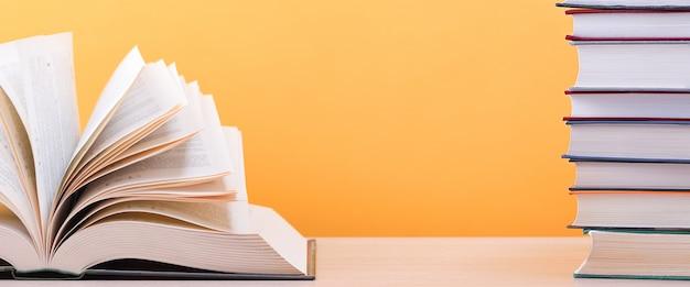 Un grande libro spesso con le pagine si allargò vicino a una pila di libri